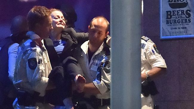 An injured hostage is carried out of a cafe in the central business district. Picture: AFP