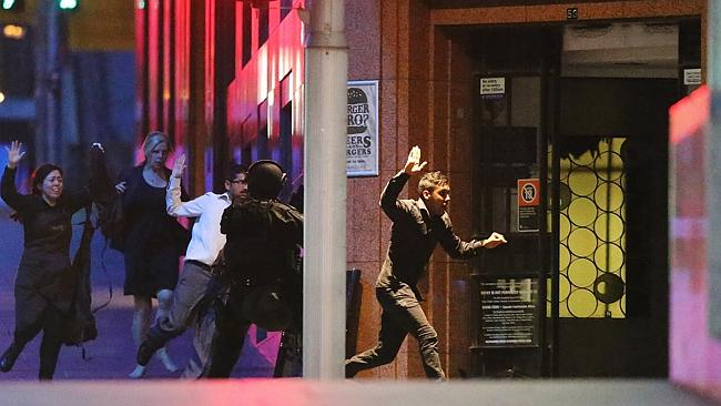 People run with their hands up from the Lindt Cafe, Martin Place. Picture: Getty Images