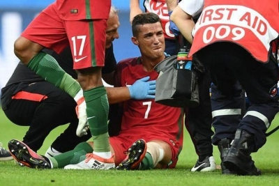 Ronaldo reacts as medics arrive on the pitch to help him off.Photograph:Franck Fife/AFP/Getty Images